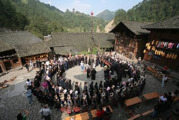 LEISHAN COUNTY, CHINA - OCTOBER 21: (CHINA OUT) Villagers of Miao ethnic origin dance with tourists at Langdeshang Village on October 21, 2006 in Leishan County of Qiandongnan Miao and Dong Autonomous Prefecture, Guizhou Province, China. With a population of 8,940,116, the Miao people is one of the largest ethnic minorities in southwest China. Qiandongnan Prefecture is a multi-ethnic region where over 20 ethnic minority groups reside. Miao and Dong minorities make up over 70 percent of its population.  (Photo by China Photos/Getty Images)